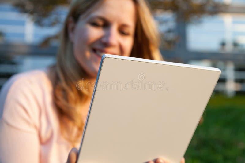 有片剂的微笑的妇女 免版税库存图片