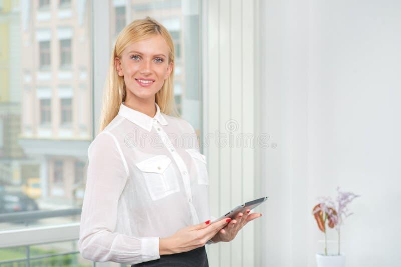 有片剂的微笑的年轻白肤金发的女实业家 图库摄影