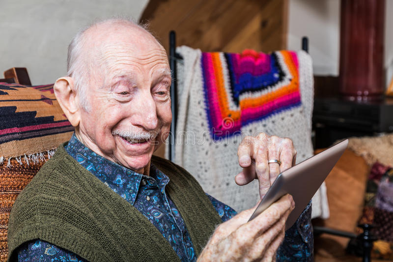 有片剂的微笑的更老的绅士 库存图片