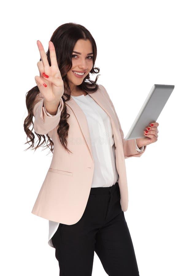 有片剂的愉快的女商人做胜利标志 免版税图库摄影