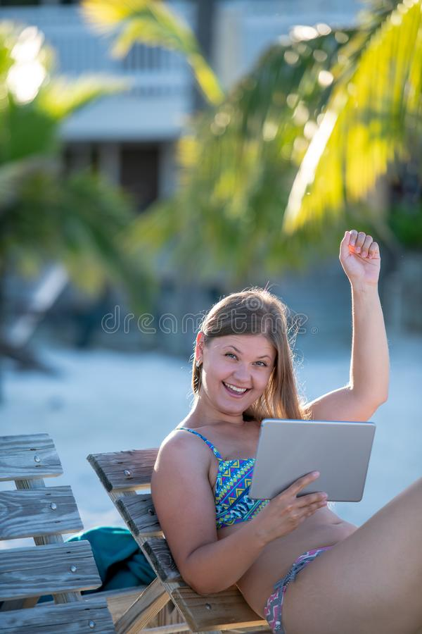 有片剂的愉快的年轻女人在海滩 库存照片
