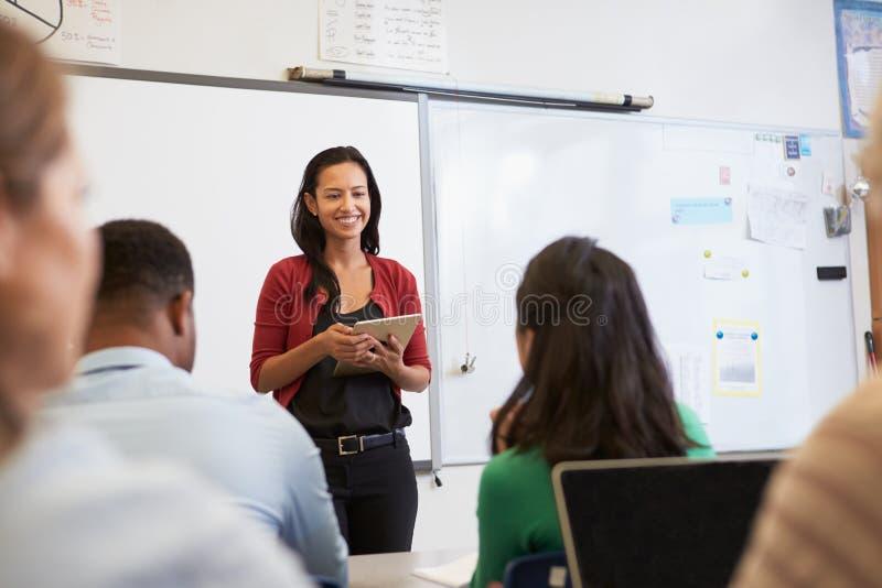有片剂的成人教育的老师和学生分类 库存图片