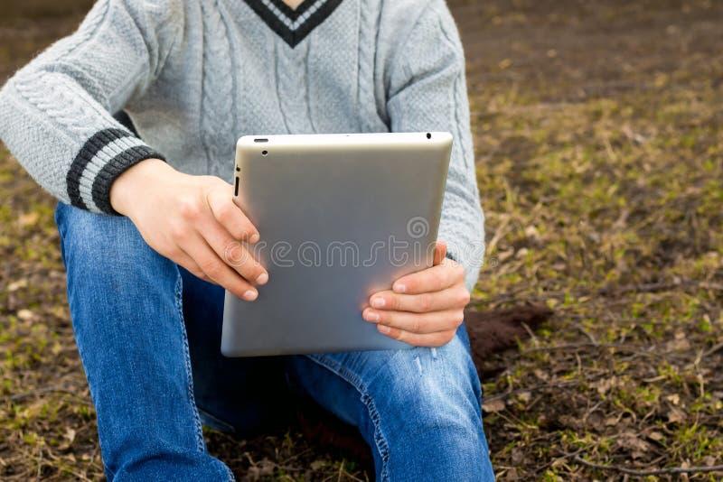 有片剂的男孩在他的手上坐草 花费时间o 免版税图库摄影