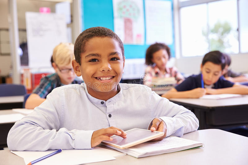 有片剂的男孩在小学类,画象 免版税库存照片