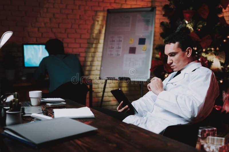 有片剂的疲乏的医生在办公室在除夕 库存照片