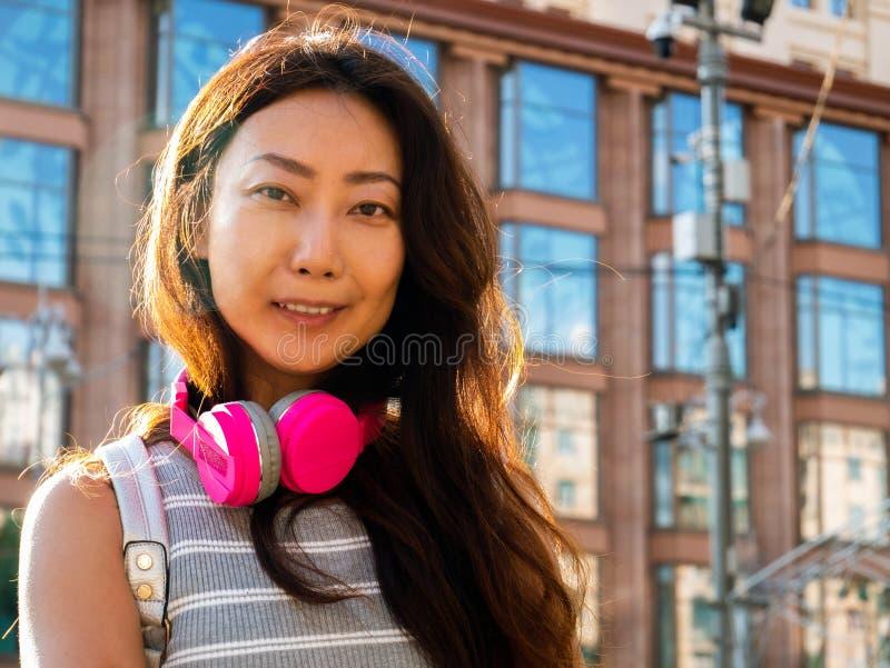 有片剂的美丽的年轻亚裔女孩 在城市身分的晴朗的夏日与耳机 库存照片