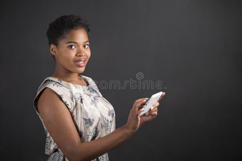 有片剂的非裔美国人的妇女在黑板背景 免版税库存图片