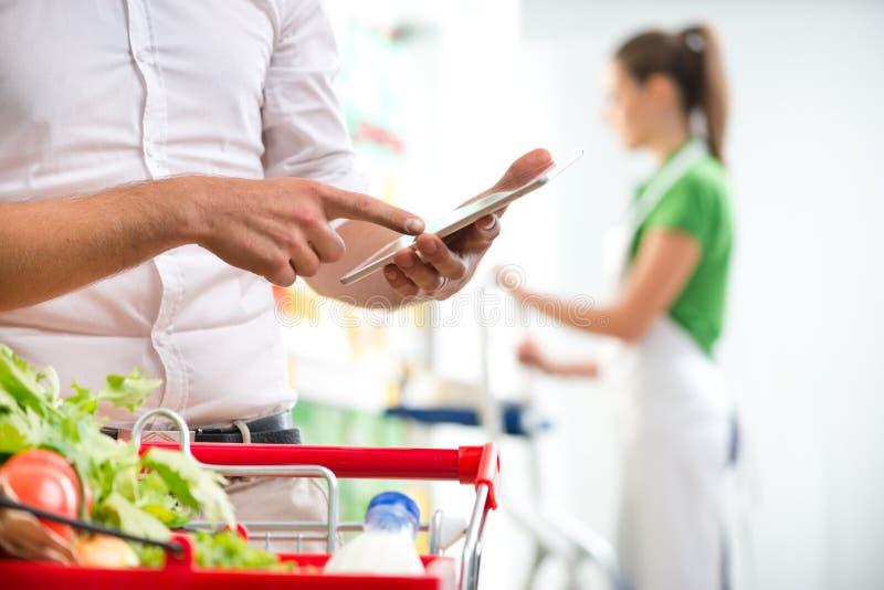 有片剂的顾客在超级市场 免版税库存照片