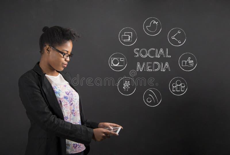 有片剂社会网络的非裔美国人的妇女在黑板背景 库存照片
