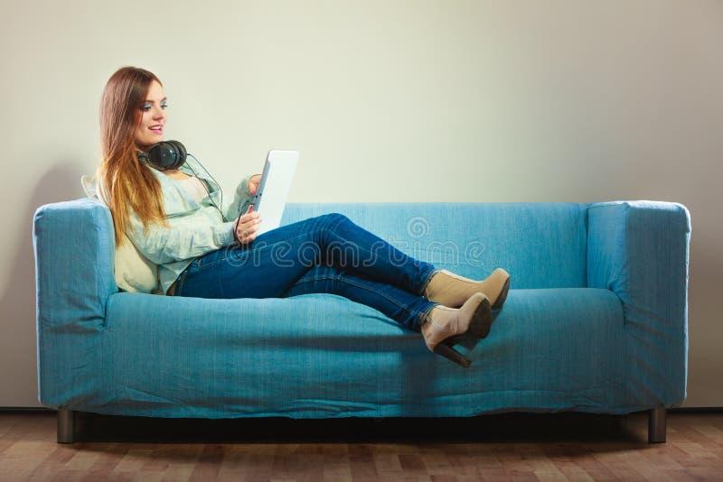 有片剂耳机的妇女坐长沙发 库存图片
