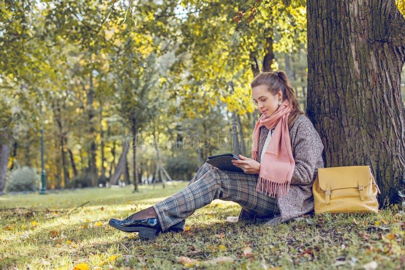 有片剂膝上型计算机的真正的女实业家在户外工作在公园 图库摄影