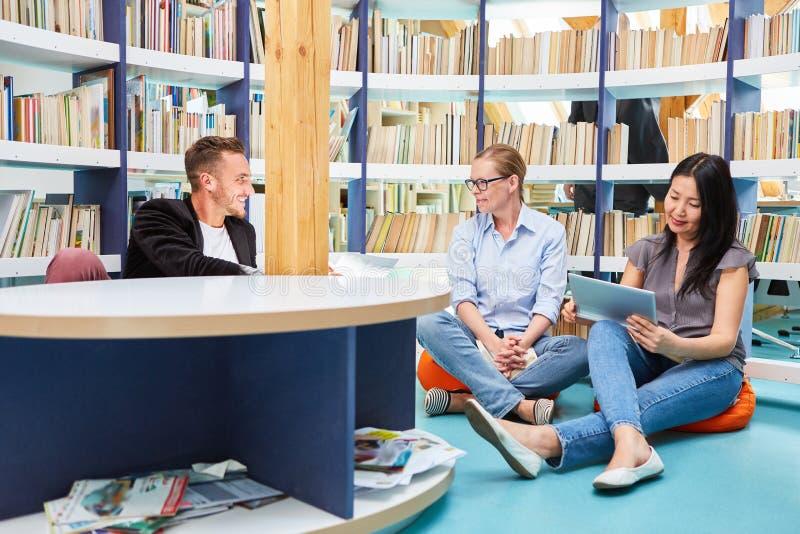 有片剂计算机的三名学生在图书馆里 库存照片