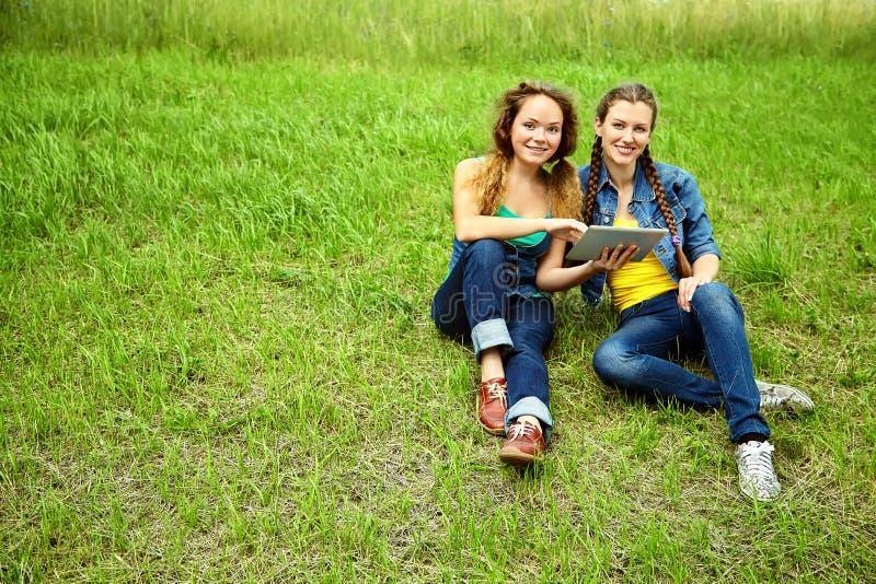 有片剂计算机的两个朋友坐草在夏天公园 青年生活方式 免版税库存图片