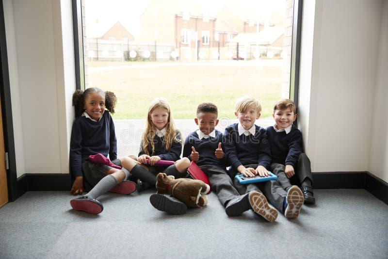 有片剂计算机的五个小学朋友坐在学校走廊的地板在休息时间,微笑对照相机,sele 库存照片