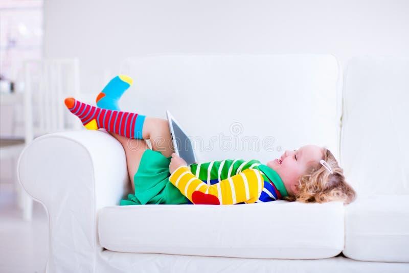 有片剂计算机的小女孩在一个白色长沙发 免版税库存照片