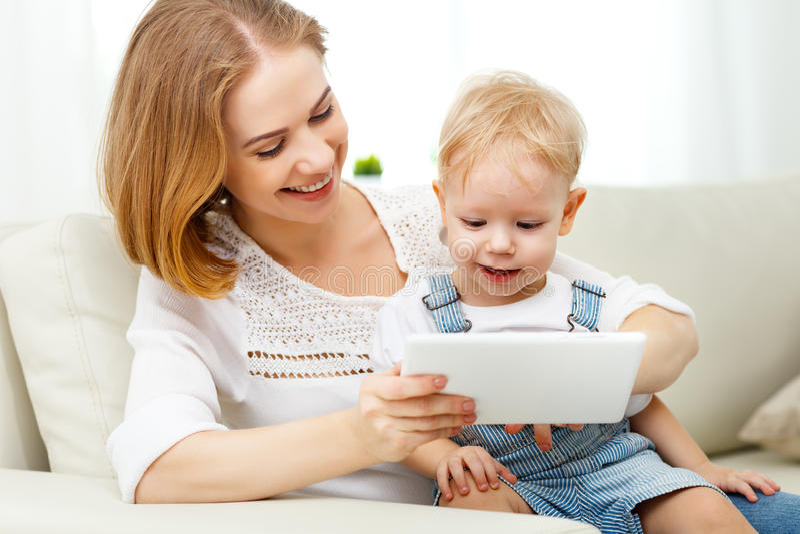 有片剂计算机的母亲和小儿子在家 免版税库存图片