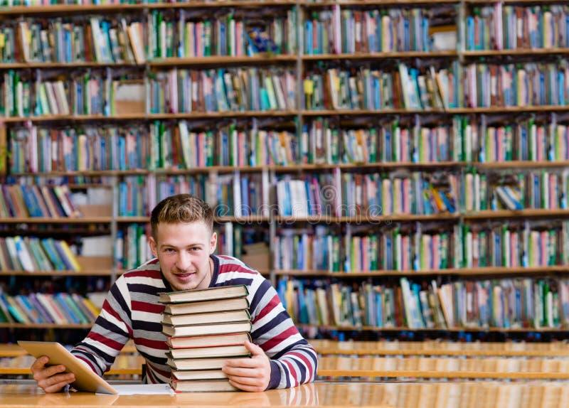 有片剂计算机的男学生在图书馆 库存照片