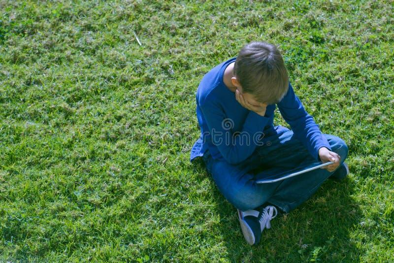 有片剂计算机的男孩坐草晴天户外 库存图片