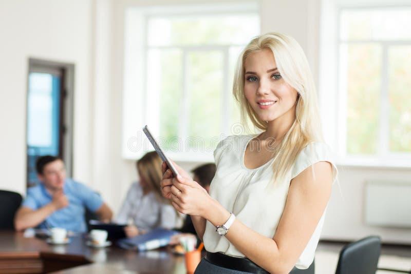 有片剂计算机的美丽的微笑的年轻白肤金发的妇女在 免版税库存照片