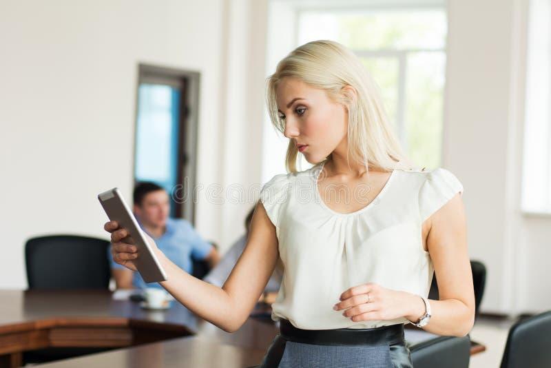 有片剂计算机的美丽的白肤金发的女孩在offic的事务 图库摄影