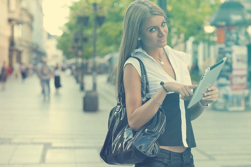 有片剂计算机的年轻女商人走在都市stree的 免版税库存图片