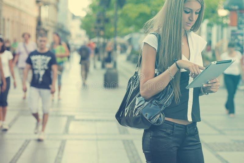 有片剂计算机的年轻女商人走在都市stree的 库存图片