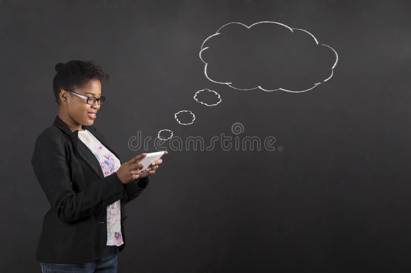 有片剂讲话的非洲妇女或在黑板背景的想法泡影 库存照片