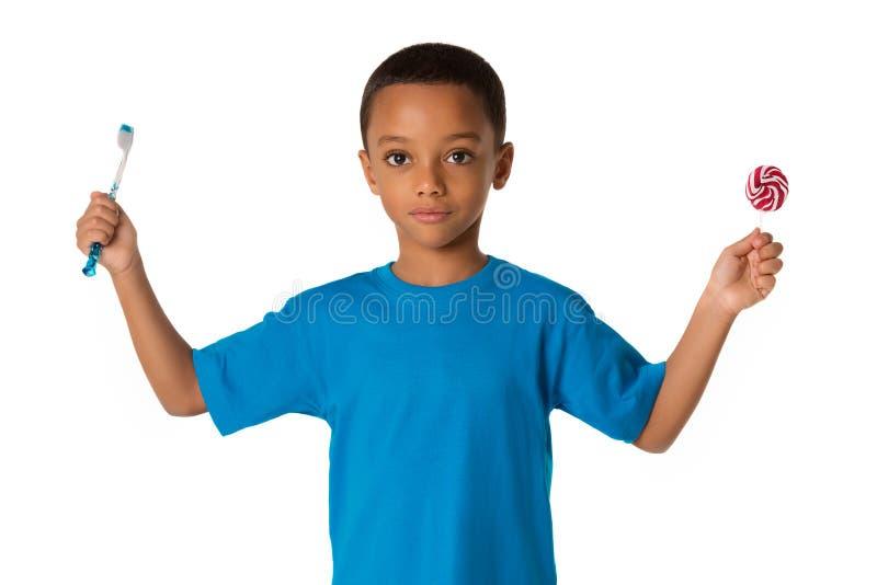 有牙刷和甜lolipop的愉快的非裔美国人的小男孩 概念健康牙 库存照片