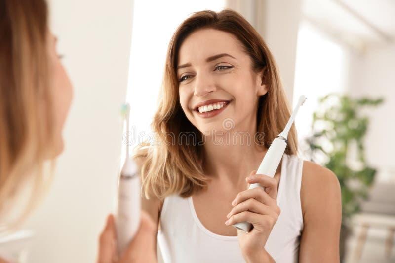 有牙刷的年轻美女在镜子附近 库存图片