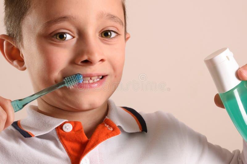 有牙刷的男孩掠过的牙在被隔绝的褐色 库存照片