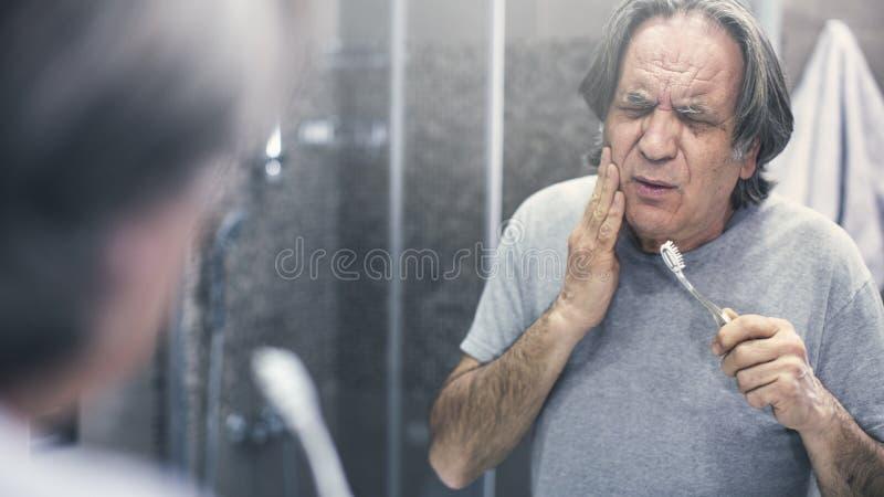 有牙痛的老人在镜子前面 图库摄影