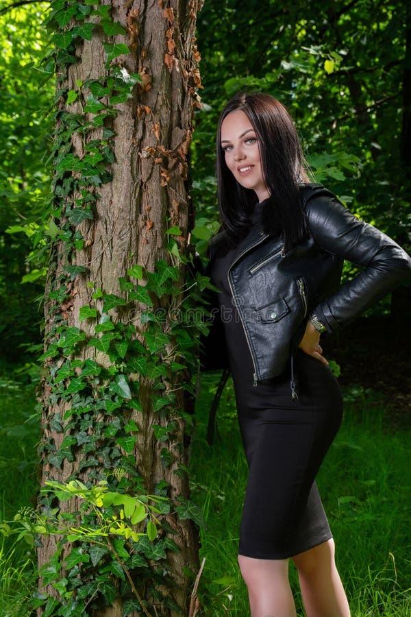 有牙的可爱的愉快的妇女在一棵树旁边微笑姿势在草的一个森林里在一个晴朗的春日 库存图片