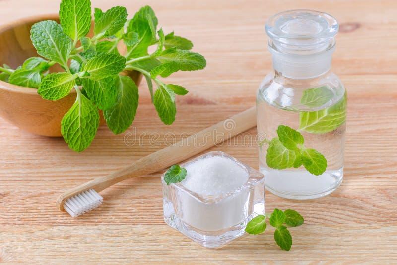 有牙膏木糖醇、苏打、盐和木牙刷特写镜头的,在木的薄菏供选择的自然漱口瓶 图库摄影