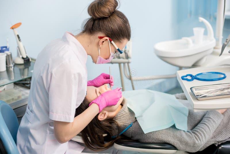 有牙齿工具的女性牙医-在牙齿诊所办公室反映并且探查对待耐心牙 免版税图库摄影