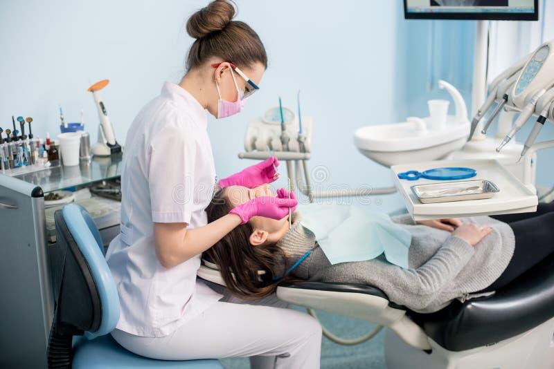 有牙齿工具的女性牙医-在牙齿诊所办公室反映并且探查检查耐心牙 库存图片