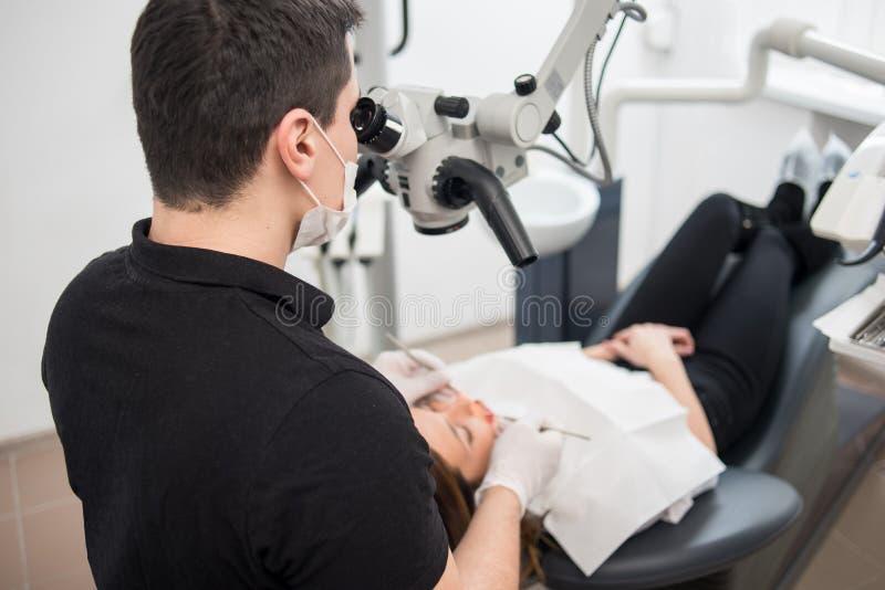 有牙齿工具的-对待耐心牙的显微镜、镜子和探针男性牙医在牙齿诊所办公室 库存图片