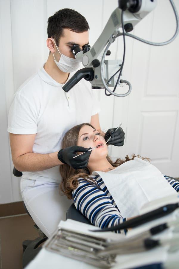 有牙齿工具的-对待耐心牙的显微镜、镜子和探针男性牙医在牙齿诊所办公室 免版税库存图片