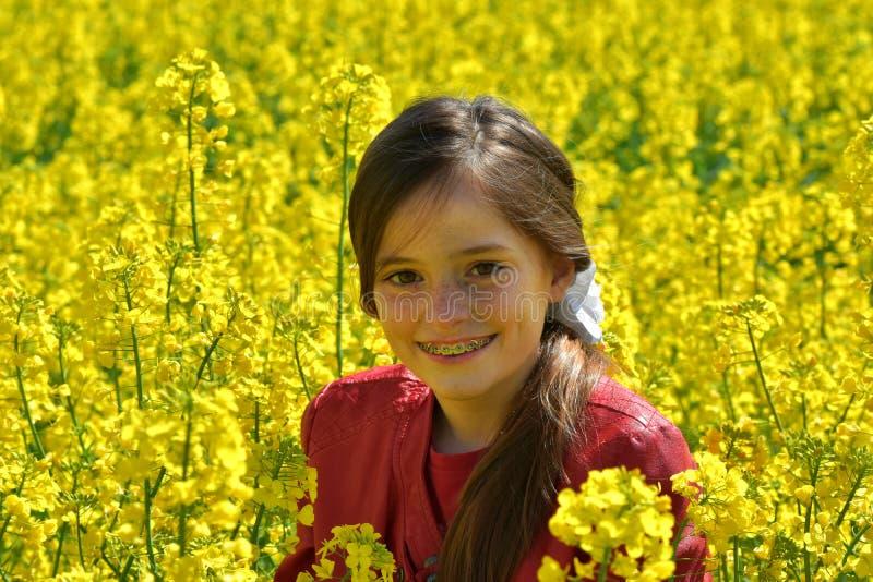 有牙齿括号的女孩在与黄色花的一个领域 免版税库存图片