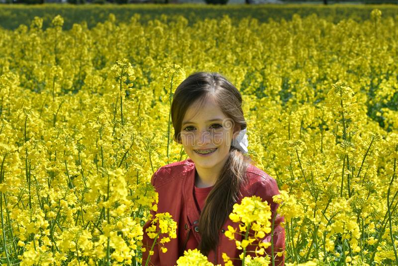 有牙齿括号的女孩在与黄色花的一个领域 图库摄影