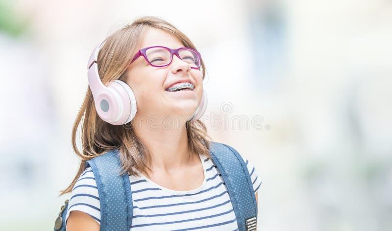 有牙齿括号的愉快的微笑的女小学生和从耳机的玻璃听的音乐 正牙医生和牙医概念 免版税图库摄影