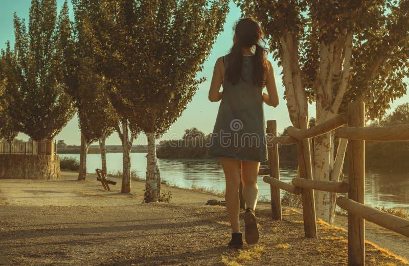 有牛仔礼服的深色的妇女走在河旁边的在日落 库存图片