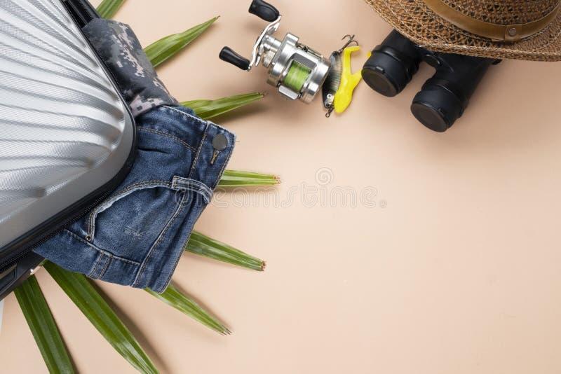 有牛仔裤的平的被放置的灰色手提箱,转动钓鱼工具,双筒望远镜,帽子,在淡色背景 旅行概念-图象 库存图片