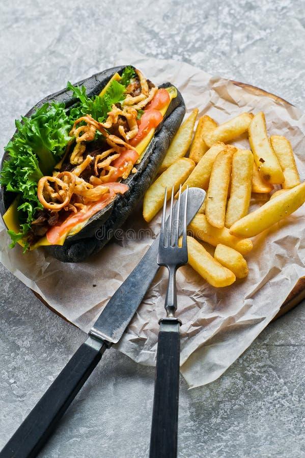 有牛肉kebab和焦糖的葱的热狗 灰色背景,侧视图 免版税库存照片