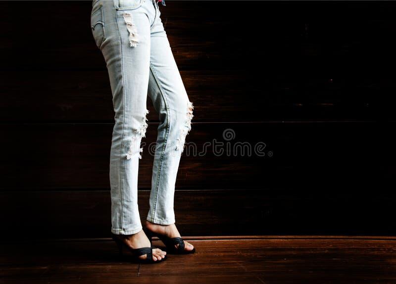 有牛仔裤的性感的夫人腿在夜总会的木酒吧 库存照片