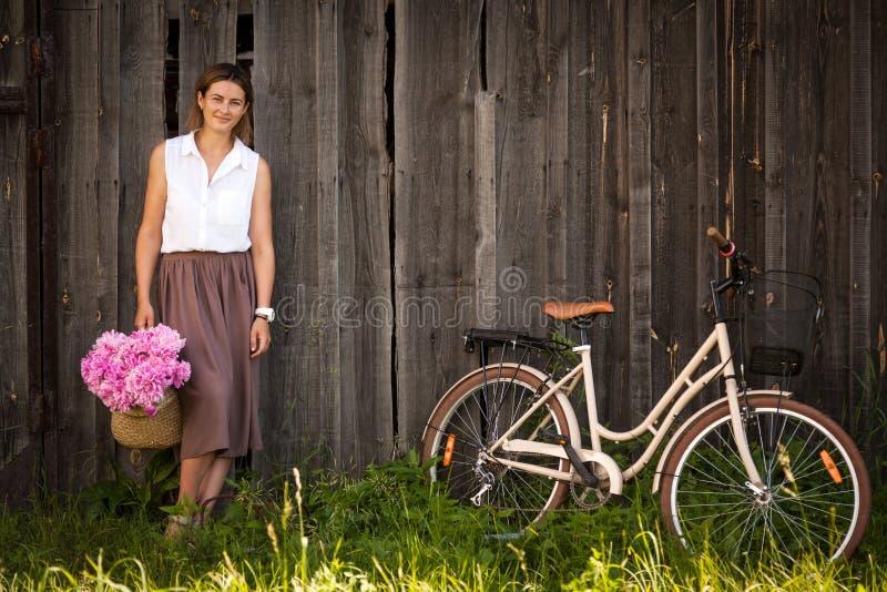 有牡丹和自行车花束的妇女  库存图片