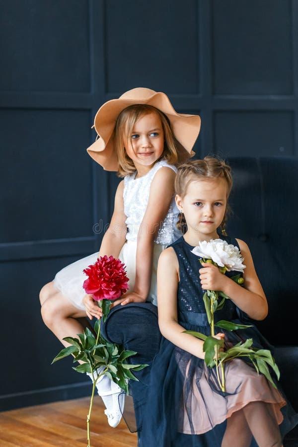 有牡丹的两个逗人喜爱的小女孩 有两个美丽的朋友乐趣,拥抱和微笑 免版税库存图片