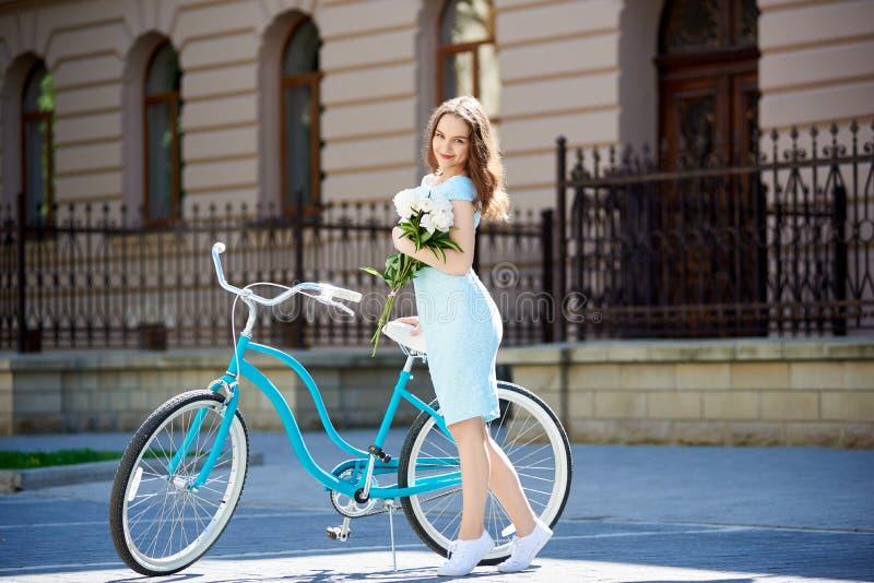 有牡丹的好妇女在蓝色减速火箭的自行车附近在阳光下 库存照片