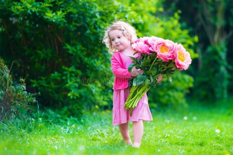 有牡丹的小女孩在庭院里开花 库存图片