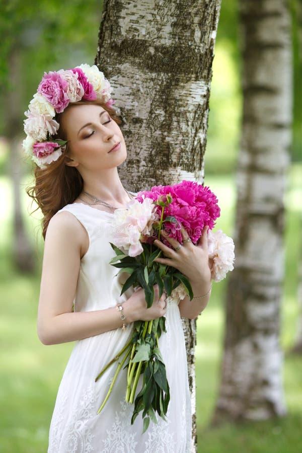 有牡丹的浪漫女孩在手上 免版税库存图片