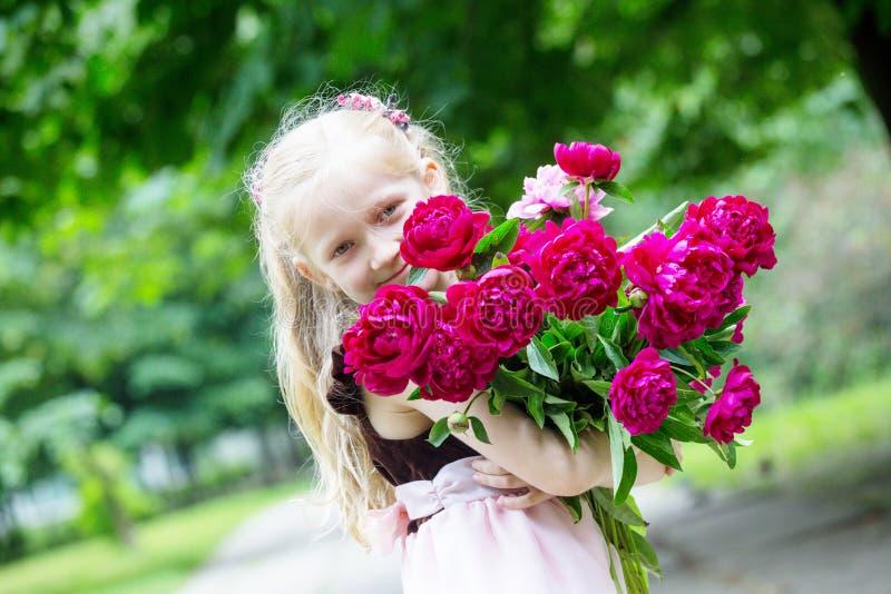 有牡丹花束的女孩  库存图片